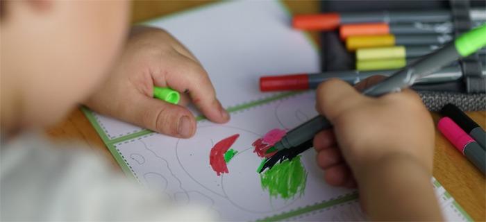 Ein Kind malt während der Langen Nacht des Schreibens 2019 eine Karte aus.
